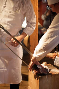 Fäviken cooks slicing meat