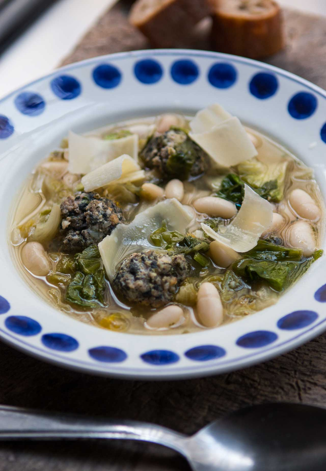 A hearty winter soup with greens, meatballs, and beans.